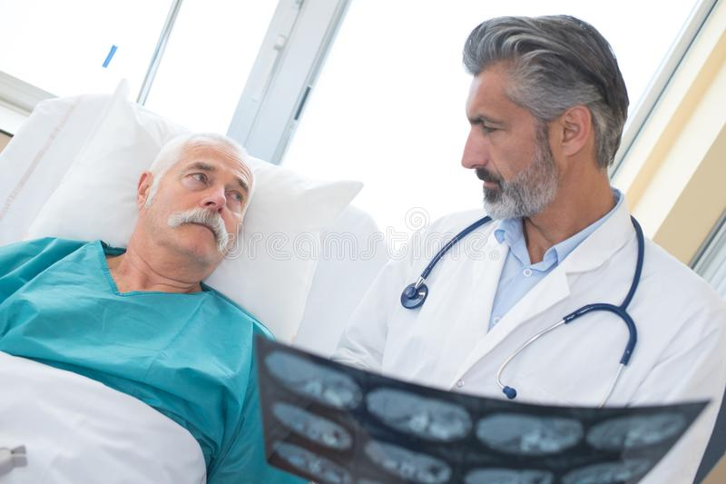 Doktor, der älteren Patienten über Röntgenstrahlen konsultiert stockbilder