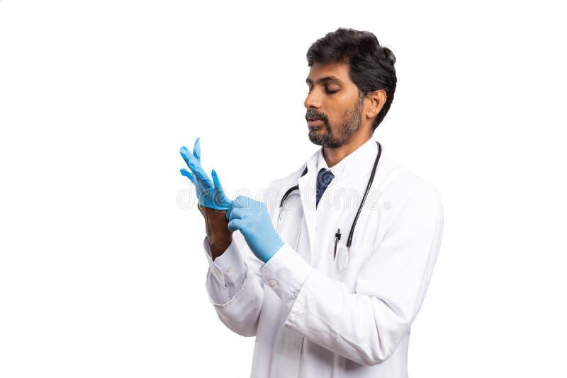 Doktor, der als Setzen auf Handschuh zur Hand schaut lizenzfreies stockbild