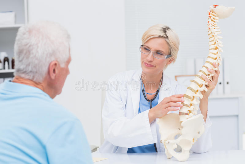 Doktor, der anatomischen Dorn zum männlichen Patienten explaning ist lizenzfreie stockfotos