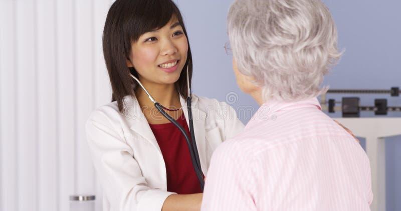 Doktor, der auf das Herz des älteren Patienten hört lizenzfreie stockbilder