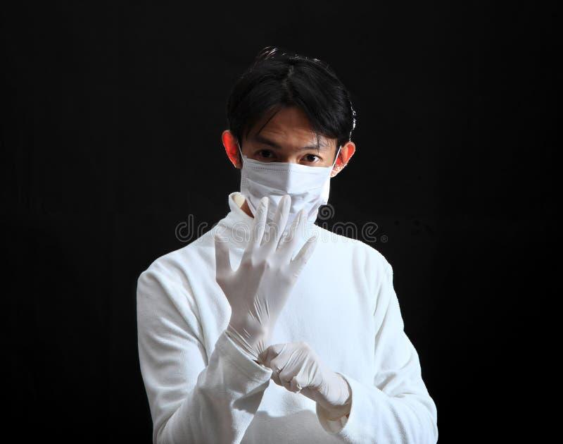 Doktor, der auf einen Latexhandschuh sich setzt stockbilder