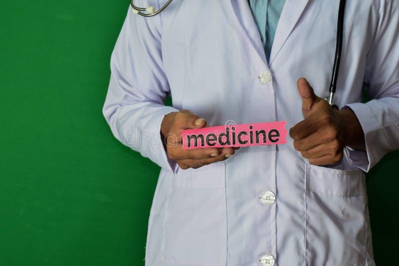 Doktor, der auf grünem Hintergrund steht Halten Sie den Medizinpapiertext lizenzfreies stockbild