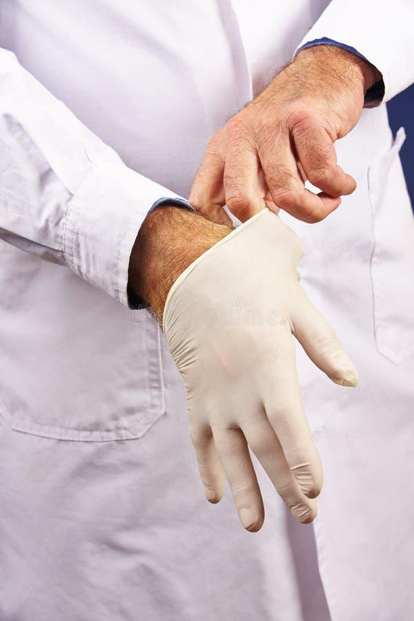 Doktor, der auf Handschuhe ins Krankenhaus sich setzt lizenzfreie stockfotografie