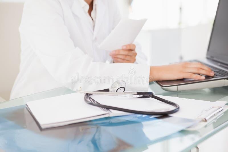 Doktor, der auf Laptop schreibt stockfoto