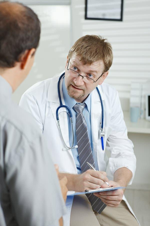 Doktor, der auf Patienten hört lizenzfreie stockfotografie