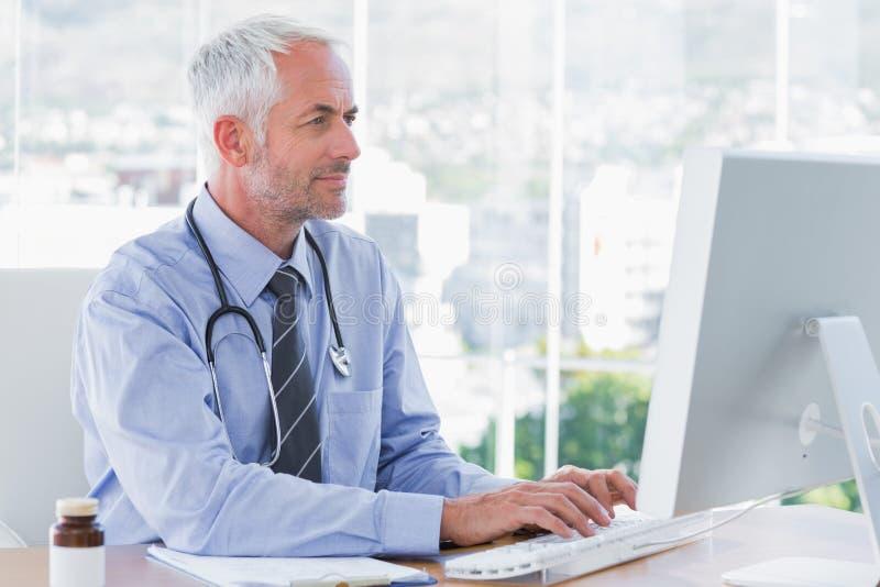 Doktor, der auf seinem Computer schreibt lizenzfreies stockbild