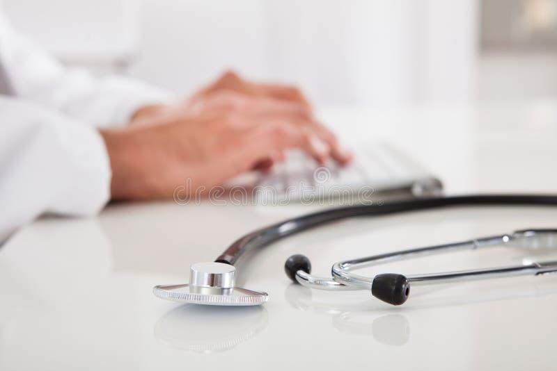 Doktor, der auf Tastatur schreibt lizenzfreie stockfotos