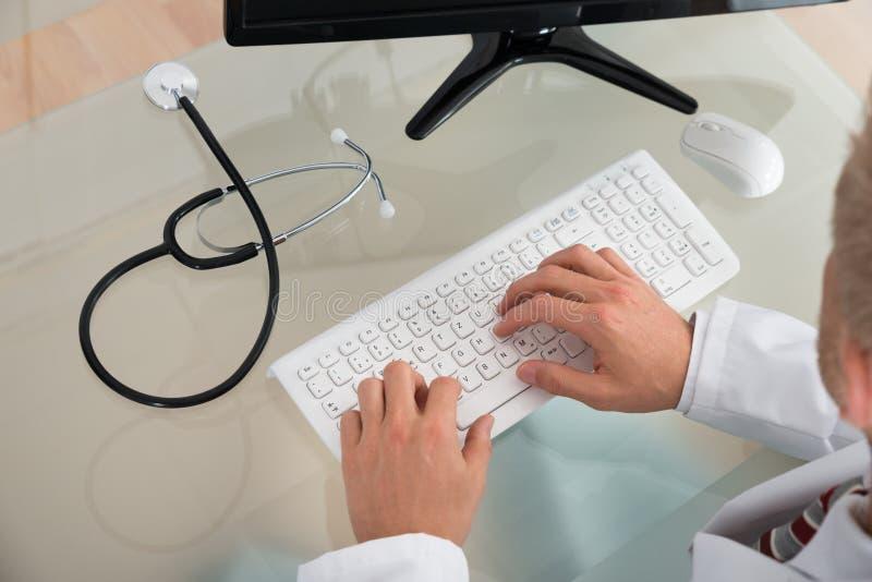 Doktor, der auf Tastatur schreibt stockbild
