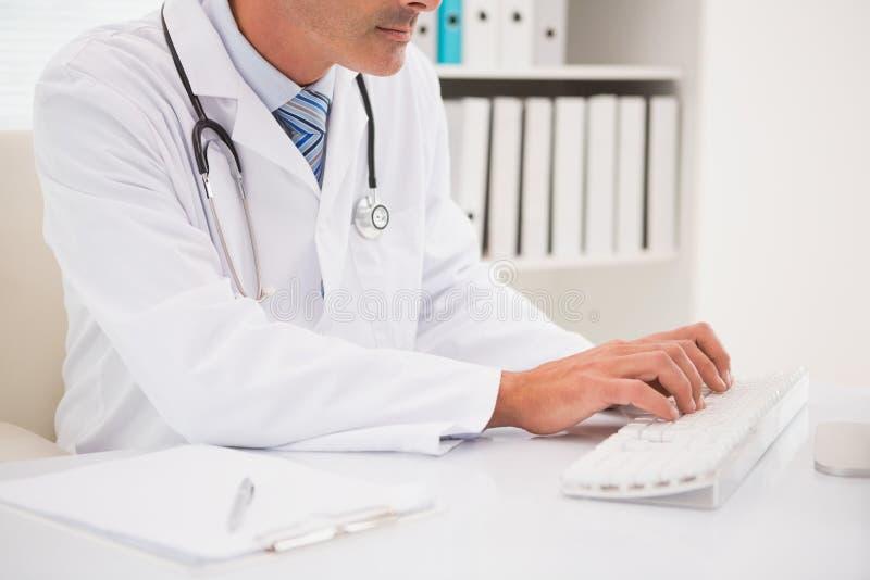 Doktor, der auf Tastatur schreibt und stockfotografie