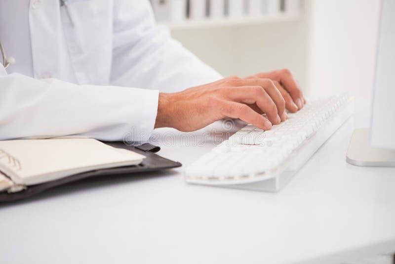 Doktor, der auf Tastatur schreibt und lizenzfreies stockfoto