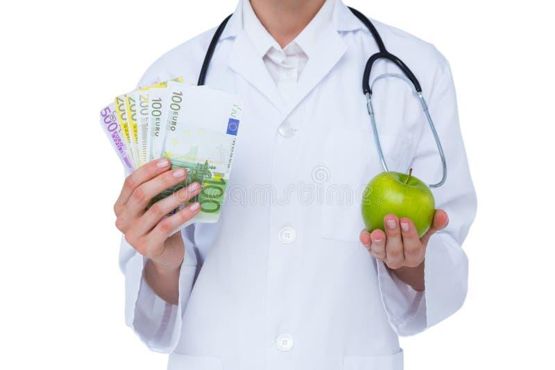 Doktor, der Bargeld und grünen Apfel hält stockbild