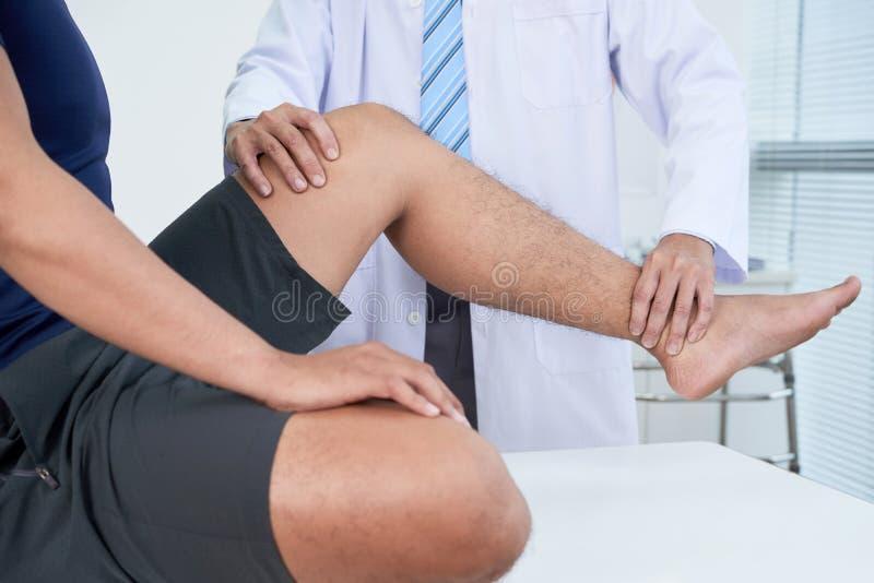 Doktor, der Bein des Patienten überprüft lizenzfreie stockfotos