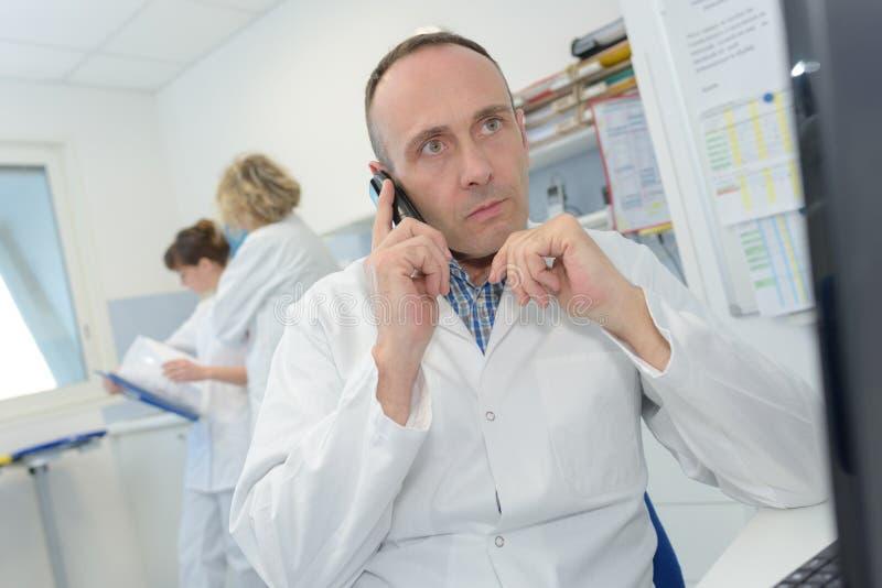 Doktor, der Bericht während am Mobiltelefon betrachtet lizenzfreie stockfotografie