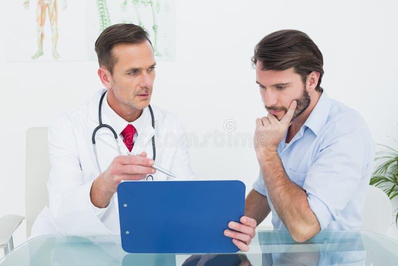 Doktor, der Berichte mit Patienten im Ärztlichen Dienst bespricht stockfotografie