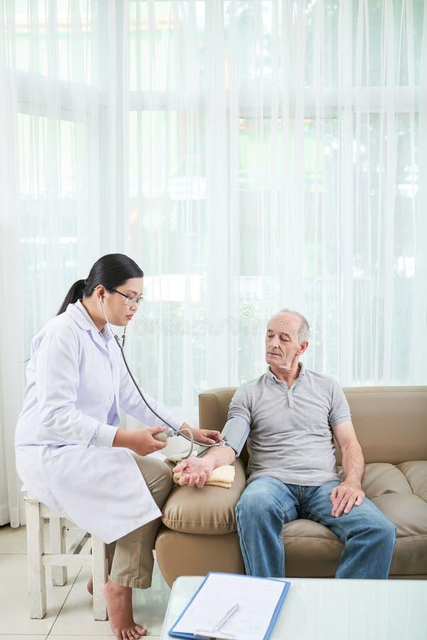 Doktor, der Blutdruck überprüft stockfoto