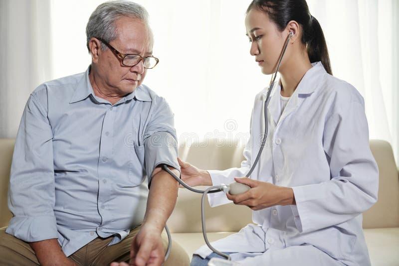 Doktor, der Blutdruck des Patienten ?berpr?ft stockbilder