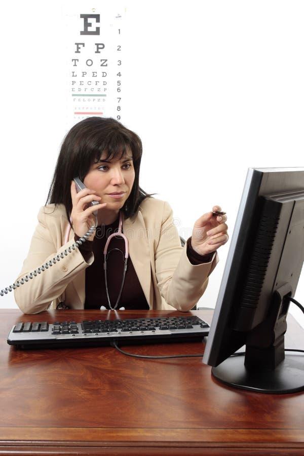 Doktor, der Computer und Telefon verwendet stockbild