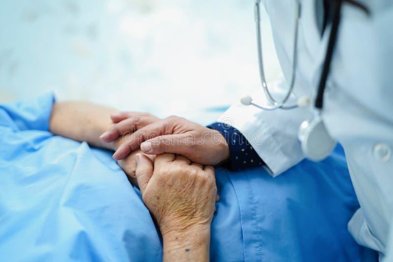 Doktor, der das Berühren Handdes asiatischen älteren oder älteren Frauenpatienten alter Dame mit Liebe, Sorgfalt hält lizenzfreies stockfoto