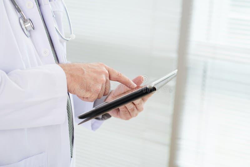 Doktor, der Daten bezüglich der digitalen Tablette überprüft stockfoto