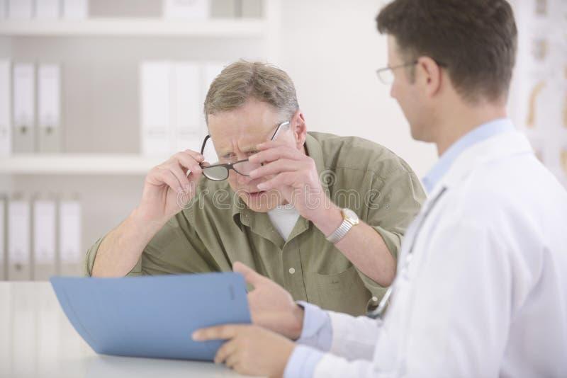 Doktor, der dem kurzsichtigen Patienten Resultate zeigt stockbild