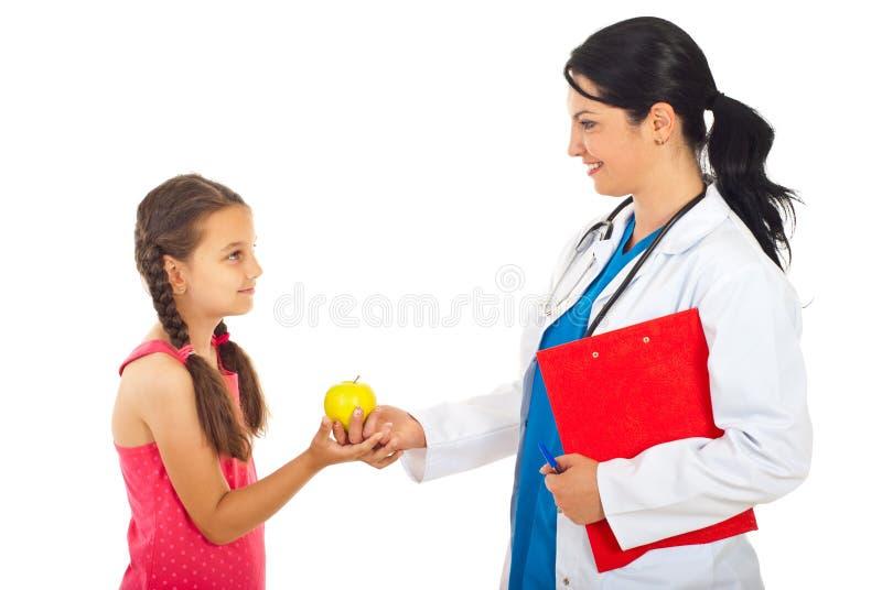 Doktor, der dem Mädchen Apfel gibt stockbilder