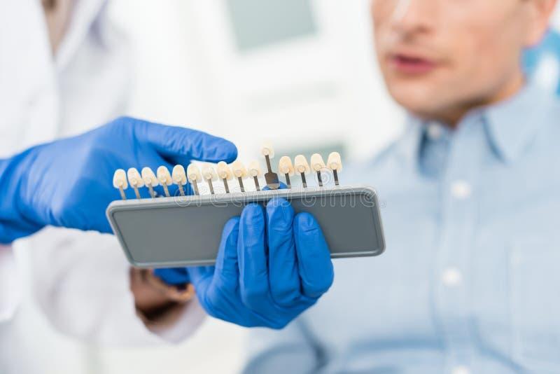 Doktor, der dem männlichen Patienten Zahnimplantate in modernem zeigt stockfotos