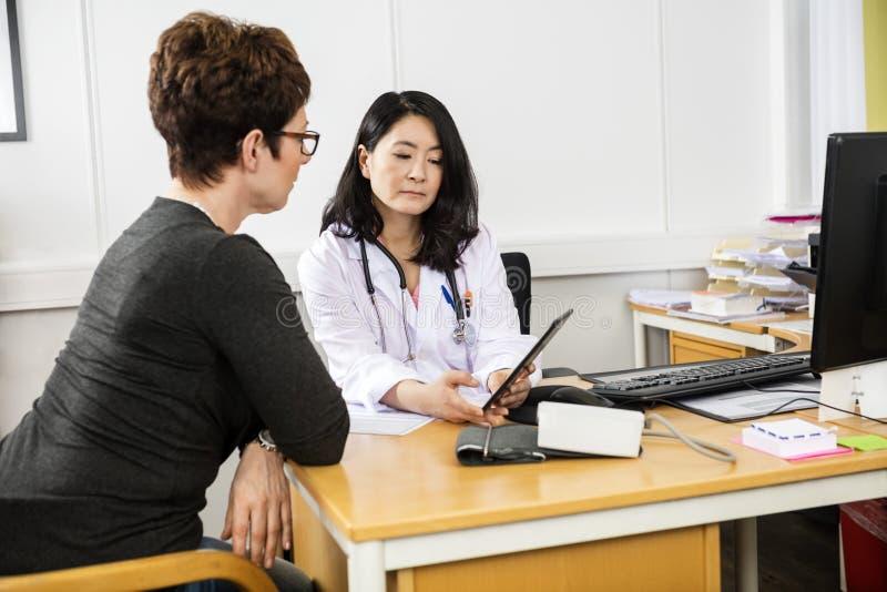Doktor, der dem Patienten digitale Tablette zeigt lizenzfreie stockfotografie