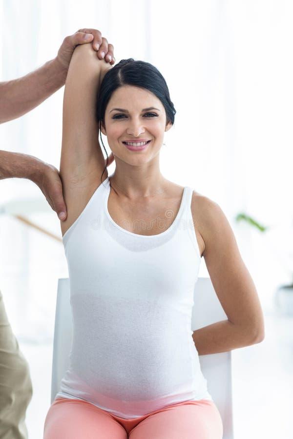 Doktor, der der schwangeren Frau Physiotherapie gibt stockfotos