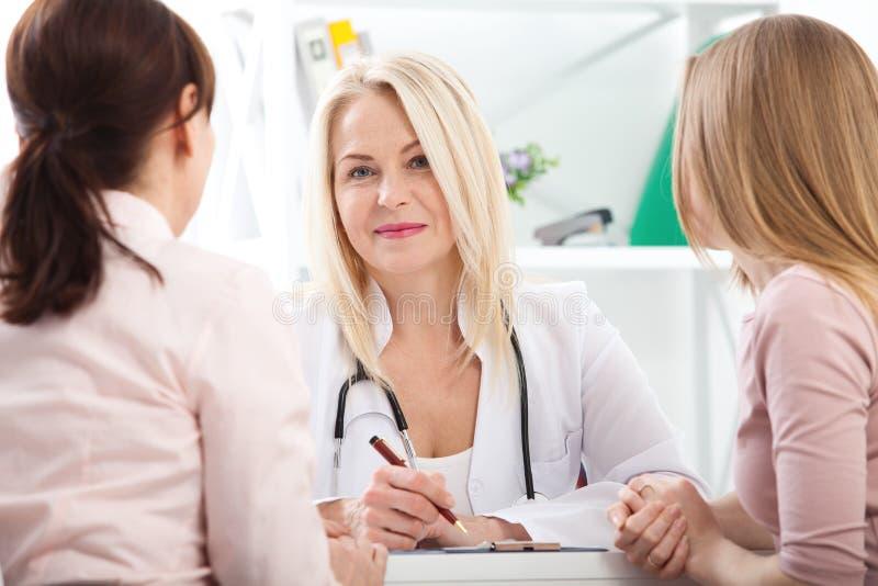 Doktor, der Diagnose ihrem weiblichen Patienten erklärt stockbild