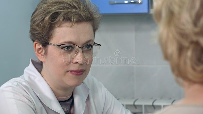 Doktor, der Diagnose ihrem weiblichen Patienten erklärt lizenzfreie stockfotos