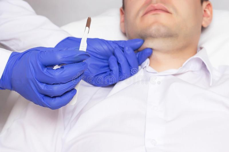 Doktor, der ein chirurgisches Skalpell auf dem Hintergrund des Gesichtes eines Mannes mit einem Doppelkinn hält Konzept der plast lizenzfreie stockfotos