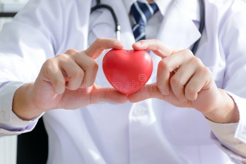Doktor, der ein Herz hält stockfotografie