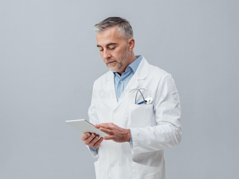 Doktor, der eine digitale Tablette verwendet lizenzfreie stockfotos