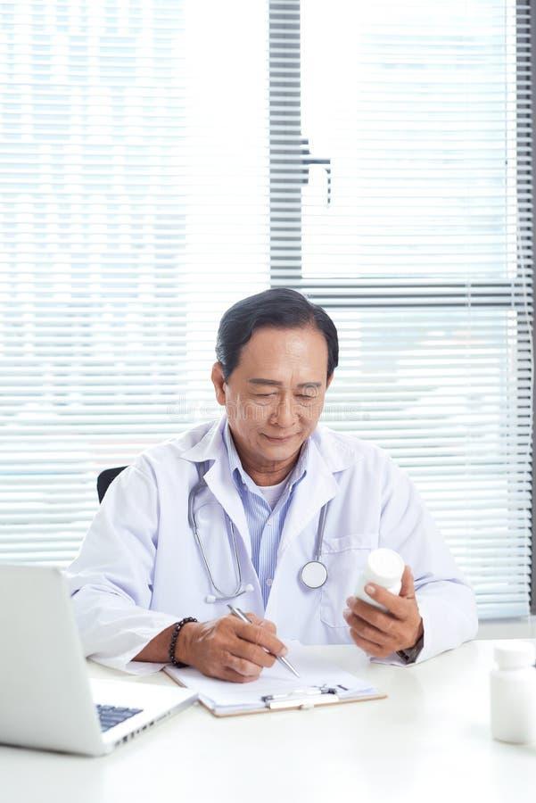 Doktor, der eine Flasche von Pillen und von seinem Anwendungslaptop hält stockfotos