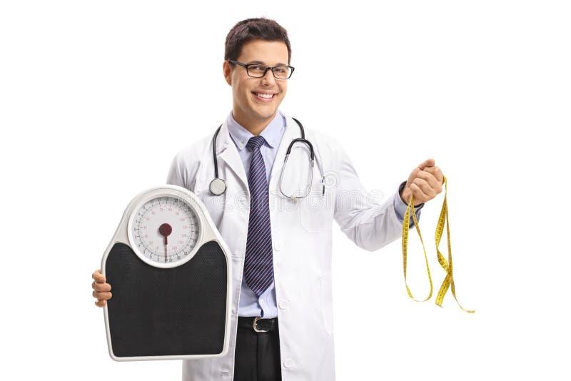 Doktor, der eine Gewichtsskala und ein messendes Band hält stockbilder