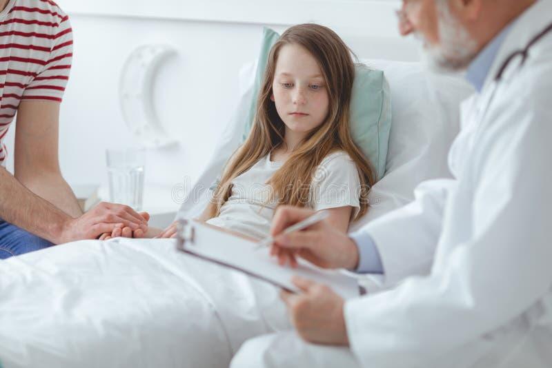Doktor, der einem Kind erklärt, wie man Medikamente nimmt lizenzfreie stockfotos