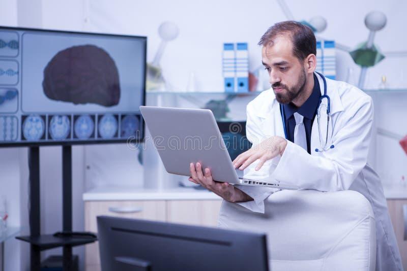 Doktor, der einen Laptop gibt einem anderen Doktor seine Sachkenntnis hält lizenzfreies stockfoto