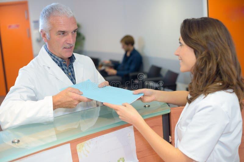 Doktor, der der Empfangsdame Datei übergibt stockfotografie