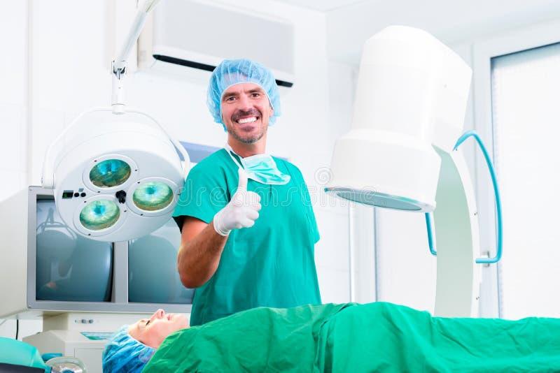 Doktor, der erfolgreiche Operation im Operationsraum hat lizenzfreie stockfotografie