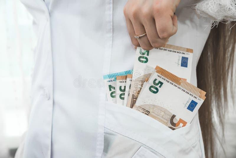 Doktor, der Eurobanknote von der Tasche auszieht stockfoto
