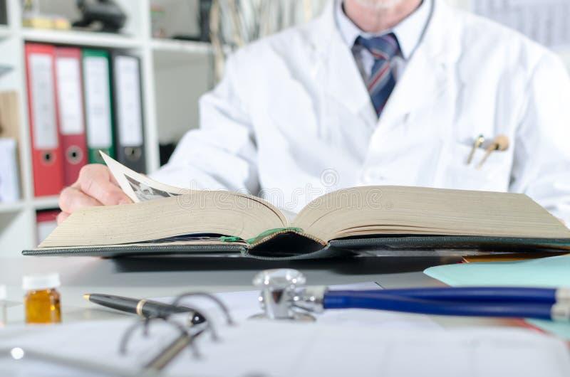 Doktor, der Forschung in einem medizinischen Buch tut stockbild