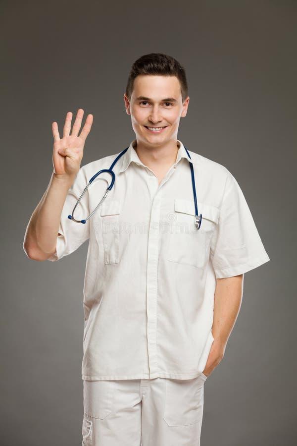 Doktor, der Friedenszeichen oder Nr. vier zeigt stockbild
