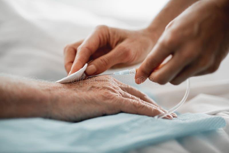 Doktor, der geduldige Hand für intravenösen Tropfenfänger vorbereitet lizenzfreie stockbilder