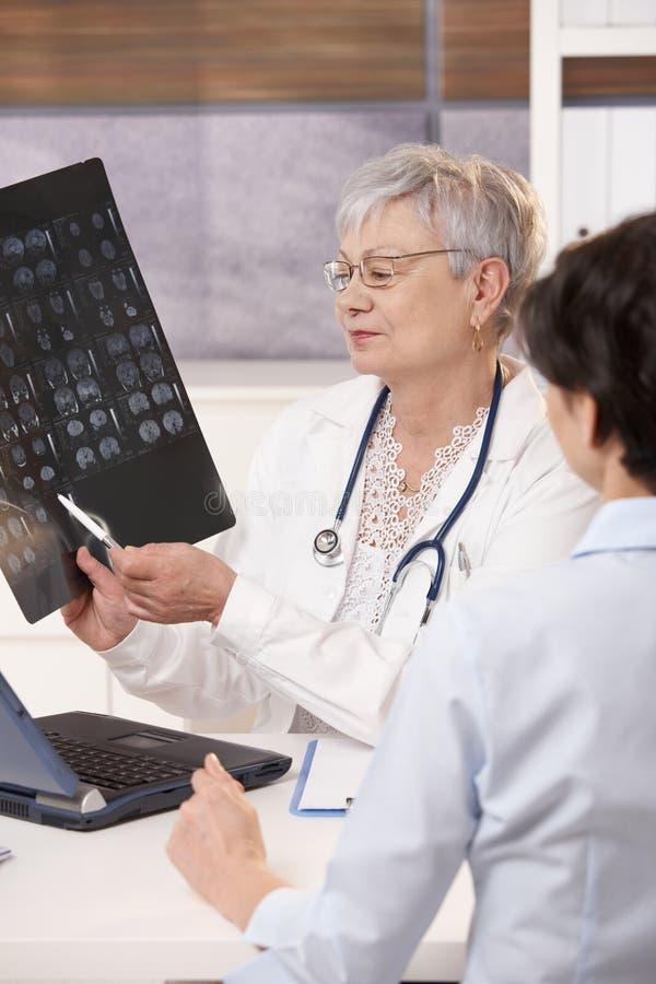 Doktor, der geduldige Scan-Resultate erklärt. lizenzfreie stockfotos