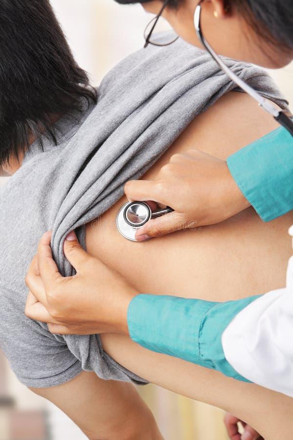 Doktor, der geduldigen Inneren Schlag überprüft stockbild