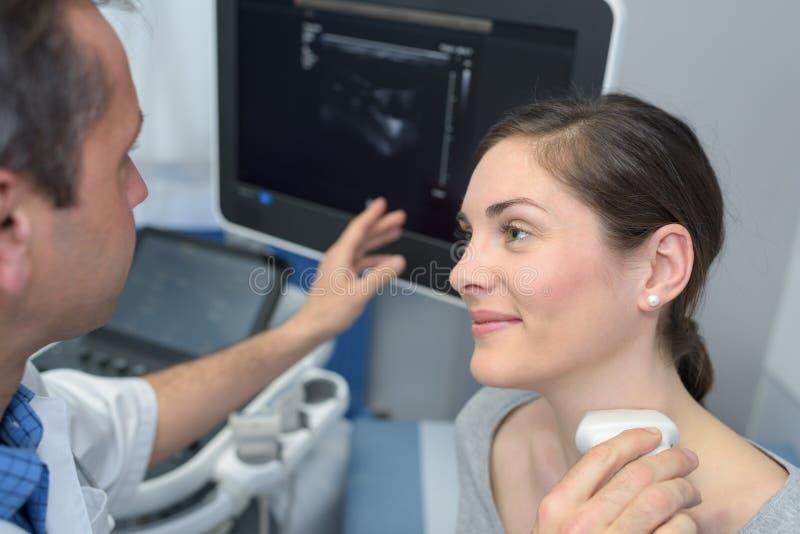 Doktor, der Halsultraschalluntersuchung auf weiblichem Patienten durchführt stockfotos