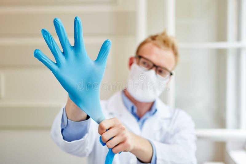 Doktor, der Handschuhe überzieht lizenzfreies stockfoto