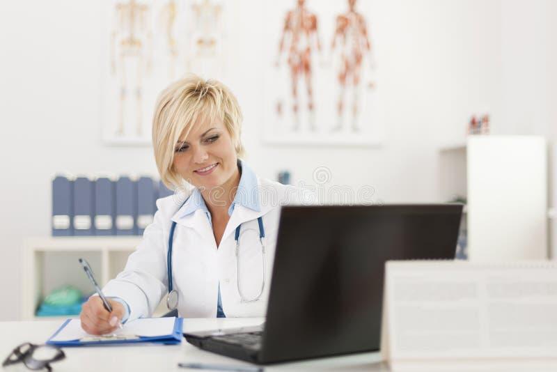 Doktor, der in ihrem Büro arbeitet lizenzfreies stockfoto