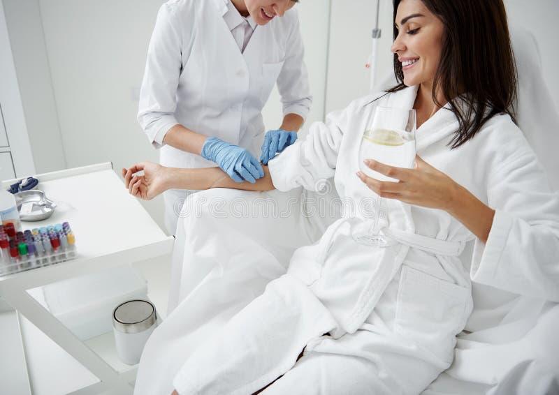 Doktor, der intravenösen Tropfenfänger auf Damenhand während sie Trinkwasser befestigt lizenzfreies stockfoto