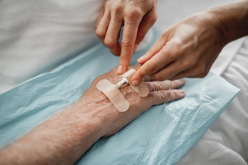 Doktor, der intravenösen Tropfenfänger auf geduldiger Hand befestigt stockfoto